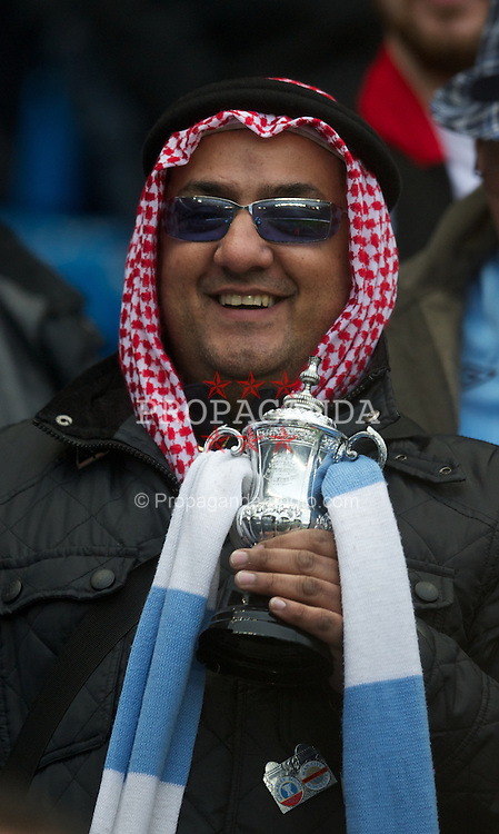 MANCHESTER, ENGLAND - Sunday, January 8, 2012: A Manchester City supporter dressed as an Arab with a miniature FA Cup trophy before the FA Cup 3rd Round match against Manchester United at the City of Manchester Stadium. (Pic by David Rawcliffe/Propaganda)