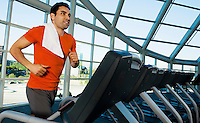 Man running on treadmill in gymnasium