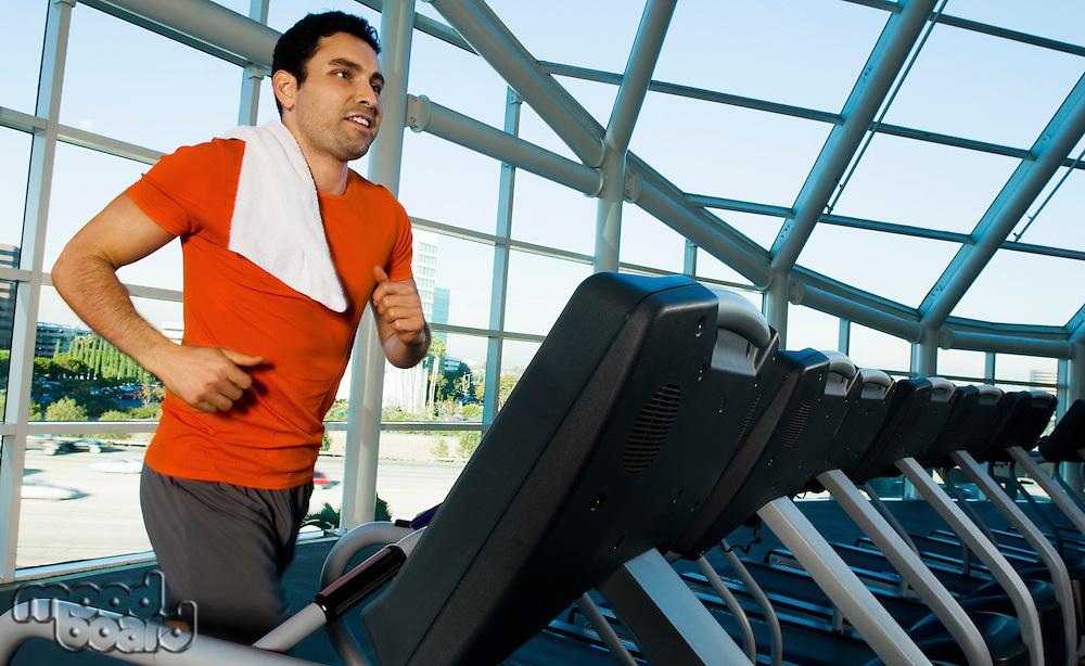 Man running on treadmill in gymnasium