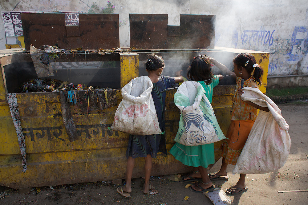 Girls including Salena (left) collect plastic from among the rotting household rubbish in a skip placed in a residential area of Lucknow.<br /><br />The rag-picking community of Shanti Busti (literally &quot;Peace Slum&quot;) which comprises 210 households have been living and working in Lucknow for the past twenty years. Originally from Assam, their language and culture differs from the wider population of Lucknow who speak Hindi. The low status of the rag-pickers' work together with their minority status as Muslims speaking Assamese makes them particularly vulnerable to stigma and discrimination. The rag-pickers also suffer insecurity of tenure over the land upon which Shanti Busti is built. Families pay a rent of INR100-150 (GB&pound;1.25-GB&pound;1.90) to a &quot;landlord&quot; who provides then some protection from eviction by the government. The community's status is further undermined by the fact that many in wider society falsely charge them with being illegal immigrants from Bangladesh. This effectively denies the rag-pickers claim to any of the rights and services afforded to other Indians including the right to vote. Without political representation the people of Shanti Busti rely on the work of Oxfam and its partners for the provision of basic services. <br /><br />Sahera Khatoon is ten years old. She lives with her two parents and five of her six siblings in a small shack built of discarded plastic sacking and bamboo poles. Sahera's father Sameer and mother Zohra arrived from Barpeta district in Assam 21 years ago. They and their families were poor landless labourers suffering the financial insecurity that comes with irregular work. Like many of their neighbours in Barpeta district, they were encouraged to make the journey to Lucknow by a refuge contractor who promised a regular income in return for their labour. It is a measure of the desperate circumstances faced by Sameer and Zohra that their life in Shanti Busti is preferable to the circumstances th