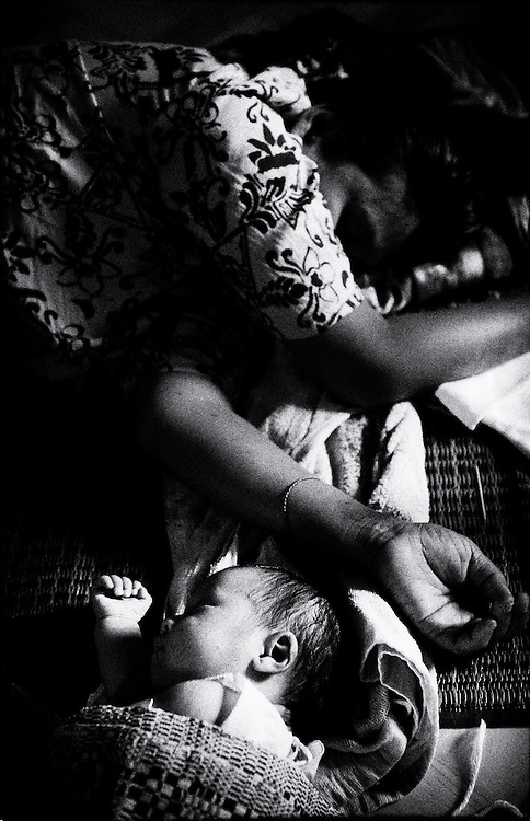 The HIV positve mother sleeps next to her HIV negative 6 week old baby at the HIV & Aids Clinic on the outskirts of Yangon (Rangoon) Myanmar (Burma) January 2012