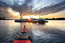 The bow of a kayak and moored sailboats at sunrise in Portsmouth Harbor in Portsmouth, New Hampshire.