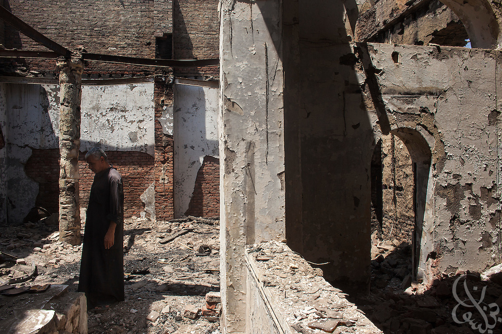 An Egyptian man walks through the still smoldering ruins of the (old) Virgin Mary Church August 20, 2013 in the village of Nazla, located near el Fayoum, and around a 100 kilometers South of Cairo, Egypt.  Christian villagers report 2 churches and a monastery in the area came under attack by their Muslim neighbors on the same day as Egyptian security forces were moving to forcibly disperse the sit-in camp of the supporters of deposed president Mohamed Morsi.