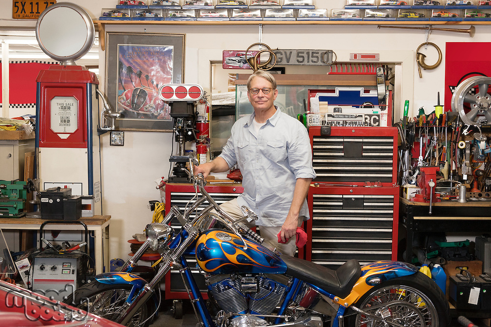 Senior man standing behind motorcycle in automobile repair shop.