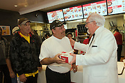 "This handout photo from KFC shows Colonel Sanders look-alike Bob Thompson serving a free two-piece Kentucky Grilled Chicken meal to Milton Scheser Tuesday, Sept. 29, 2009 at a Louisville, Ky., KFC restaurant that has been converted into a ""World Hunger Relief Kitchen"" during the lunch rush to feed residents of the local Wayside Christian Mission. KFCs across the country will be collecting donations for World Hunger Relief now through the end of October. (Photo by Brian Bohannon)"