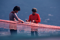 fishermen repairing nets in Cefalu, Sicily