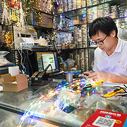 A man fixes  decorative lights at his shop in Shenzhen, a hightech hub in southern China.