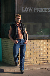 blond man without a shirt in a sleeveless leather jacket leaning against a building