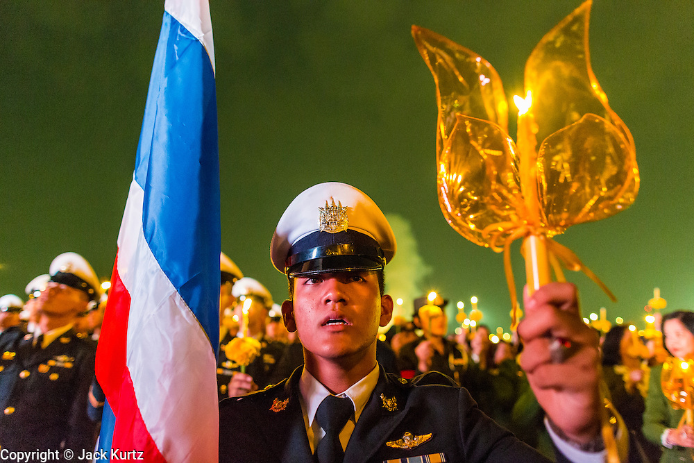 05 DECEMBER 2013 - BANGKOK, THAILAND: A member of the Royal Thai Air Force holds up a candle during a celebration of birthday of the King. Thais observed the 86th birthday of Bhumibol Adulyadej, the King of Thailand, their revered King on Thursday. They held candlelight services throughout the country. The political protests that have gripped Bangkok were on hold for the day, although protestors did hold their own observances of the holiday. Thousands of people attended the government celebration of the day on Sanam Luang, the large public space next to the Grand Palace in Bangkok.     PHOTO BY JACK KURTZ