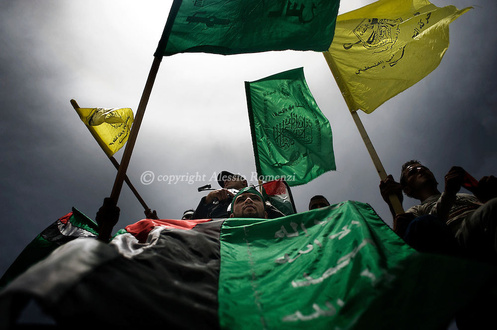 GAZA CITY : Palestinians wave Fatah and Hamas flags as they celebrate the unity deal between rival factions Hamas and Fatah on May 4, 2011 at the Unknown Soldier square in Gaza City where the yellow flag was allowed to be seen for the first time since 2007 as a reconciliation deal was signed by the rival movements in Cairo.ALESSIO ROMENZI