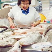 Fishmonger preparing the for a customer at Ribeira market.