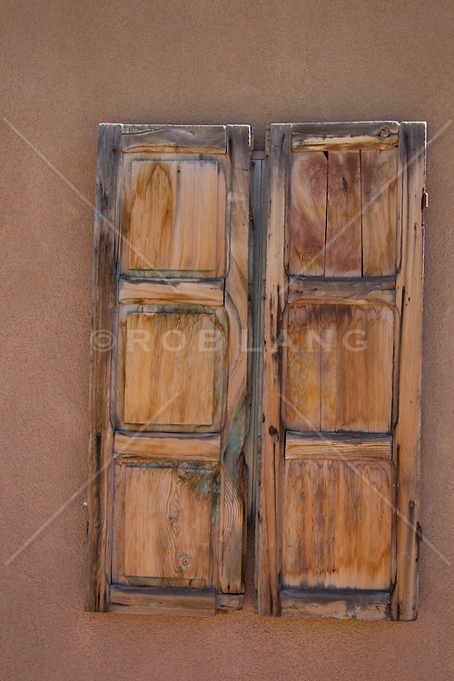 hand carved wooden shutter doors on a window in New Mexico