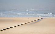 People walking on wide empty sandy beach at Frinton on Sea, Essex, England