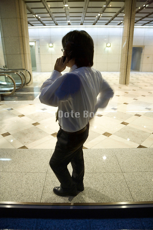 young businessman leaning against window while talking on his cellphone