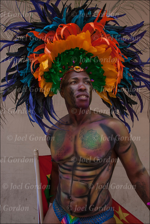 Portrait of person of color from Caribbean wearing rainbow pride colorful feathers headdress showing both his Carnival ethnic and gender pride during the Gay Pride Parade 2014 in New York City.