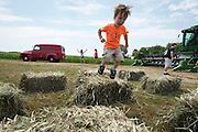 Willem Fuller, 4, leaps from a hay bail during the fourth annual International Student Farm Outing at the Schultz Family Farm in Cottage Grove, Wis., on June 24, 2012. Co-sponsored by the Schultz family and the University of Wisconsin-Madison International Student Services (ISS), the event introduced more than 100 UW-Madison international students and their families, and friends of the Schultz family to agricultural life in rural Wisconsin.