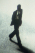 Blurry shot of a male executive walking across the street