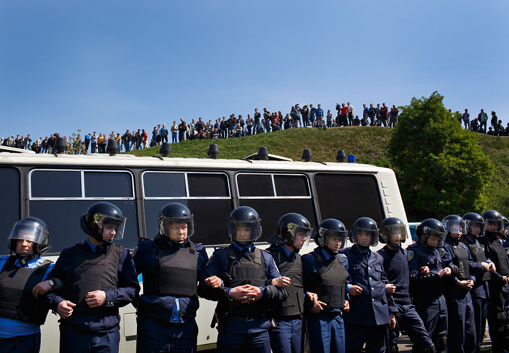 Members of Ukrainian law enforcement link arms to protect a bus containing detained ultra-nationalists outside of a rally by the Ukrainian communists on May 1, 2015 in Kyiv, Ukraine.