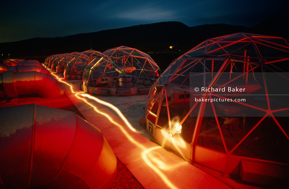 On a dark evening in the Welsh countryside eight ventilated hemispherical glasshouses called Solardomes have been 'painted' with gels and with coloured flash strobes while a torch has streaked whiter light in this scientific facility. Replicating climate change and its effects on plant-life, this experiment run by the University of Aberystwyth has run for 20 years, its research being invaluable to our understanding how rising levels of greenhouse gases (CO2) will affect photosynthesis and therefore plant food growth. By increasing the levels of such gasseous pollutants are we now more sure of how the biology in seminatural grasslands alters. Glowing red, the Solardomes sit like futuristic houses on another planet. Surrounding hills are dark on this evening but there is still detail in the fast-fading sky. ..