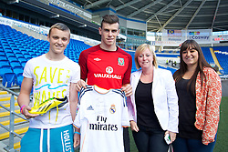 CARDIFF, WALES - Monday, September 9, 2013: Wales' Gareth Bale signs a shirt for supporter Scott Abbruzzesse after a training session at the Cardiff CIty Stadium ahead of the 2014 FIFA World Cup Brazil Qualifying Group A match against Serbia. (Pic by David Rawcliffe/Propaganda)