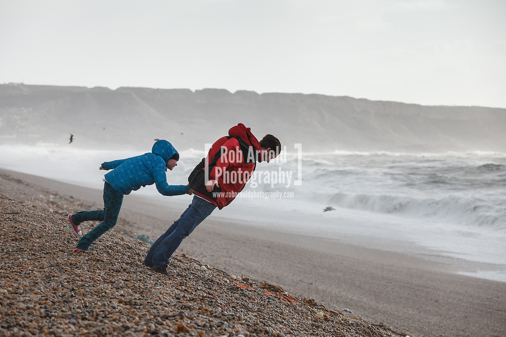 08/02/2014 - Chesil Beach, Dorset, UK - A man and boy lean into the strong winds blowing in from the English Channel during a period of stormy weather. Photo by Rob Arnold