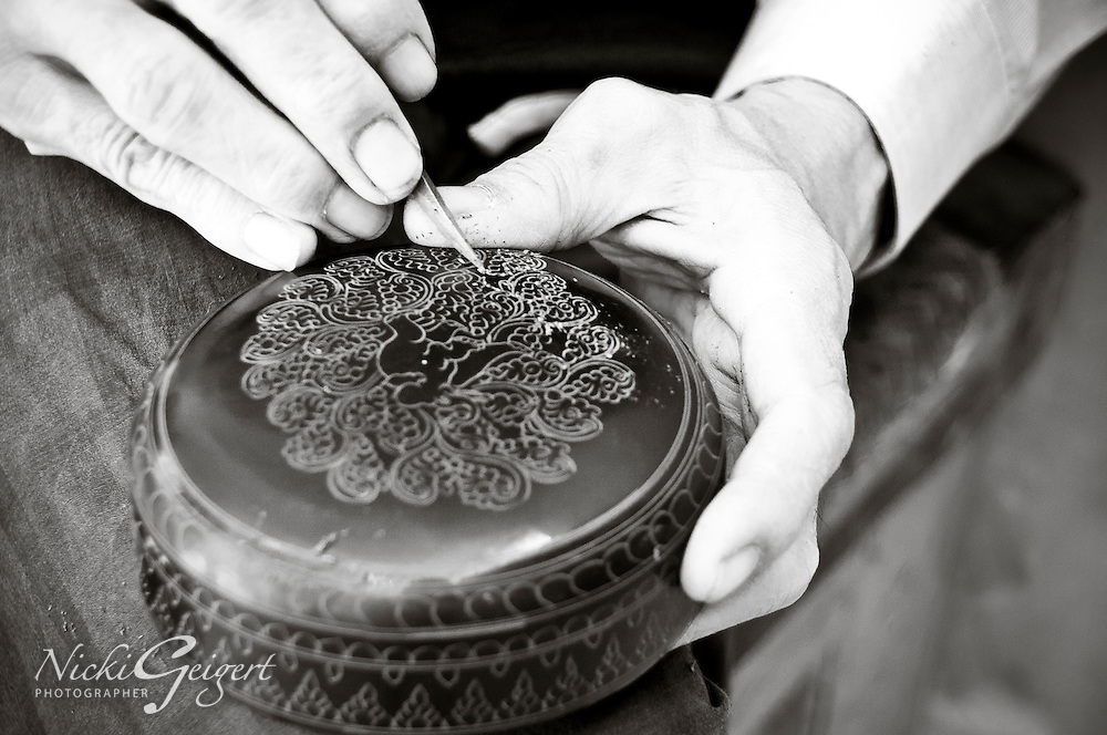 Artisan hand-crafting decorations on a container, black and white, India. Fine art photography prints for sale