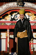 "A staffer wearing traditional garb stands in front of Houshinmon Gate inside the grounds of Shuri-jo Castle in Naha, Okinawa Prefecture, Japan, on June 24, 2012. Houshomon is the final gate leading to the main ""Seiden"" hall, a detail of which can be seen in the background. Photographer: Robert Gilhooly"