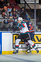 KELOWNA, CANADA - DECEMBER 27: Carsen Twarynski #18 of the Kelowna Rockets checks Carson Denomie #34 of the Kamloops Blazers into the boards on December 27, 2017 at Prospera Place in Kelowna, British Columbia, Canada.  (Photo by Marissa Baecker/Shoot the Breeze)  *** Local Caption ***
