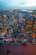The View of Manhattan from the Top of the Rock, the observation deck at the top of Rockefeller Center, New York City, NY with a view of the Empire State Building at dusk.