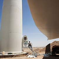 A massive wind turbine rotor blade is secured to the ground  while workers construct the tower, left, at the Xiang Yang Windfarm outside of Anxi, Gansu province. Workers must wait for a lull in the wind before raising the turbine and blades atop the supporting tower.