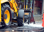 © Licensed to London News Pictures. 06/10/2014. Twickenham, UK. The bucket of a digger was used to stem the flow.  Firefighters help to contain a mains water pipe which has burst in King Street Twickenham today 6th October 2014. It appears that workmen working in the area have used a JCB digger to stem the flow. Many local shops and businesses have been flooded.   Photo credit : Stephen Simpson/LNP