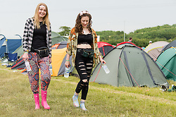© Licensed to London News Pictures. 12/06/2015. Isle of Wight, UK.  Female festival goer wearing flower headbands and welllies walk through the campsite of Isle of Wight Festival 2015 on the morning of Friday Day 2.  Yesterday the weather was hot and Sunny.  Today rain is forecast.  This years festival include headline artists the Prodigy, Blur and Fleetwood Mac.  Photo credit : Richard Isaac/LNP
