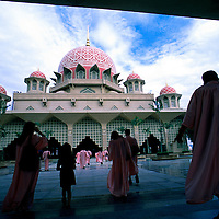 Tourists walks inside the compound of Putra Mosque in Putrajaya, Malaysia..Putra Mosque in Putrajaya reflects the evolution of mosque design in Malaysia, with its Islamic inspired architecture. Putrajaya is the Malaysia's administrative capital.