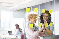 Business women brainstorming with sticky notes in office
