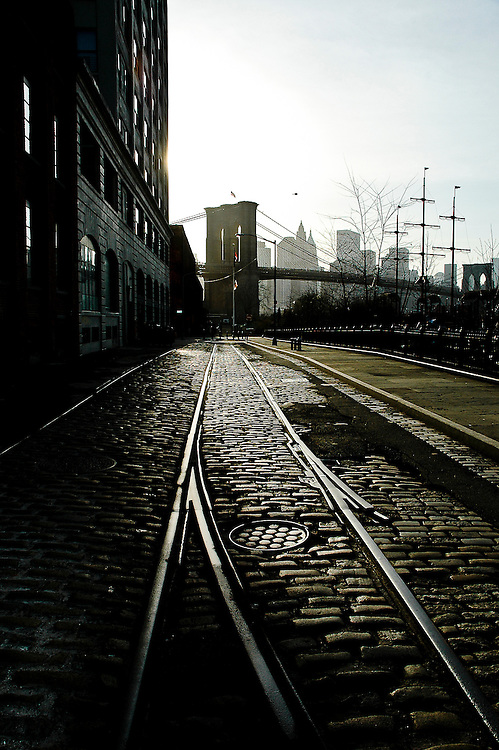 The paved Water street in DUMBO, Brooklyn, with the old railroad tracks and the Brooklyn Bridge at sunset, New york, 2008.
