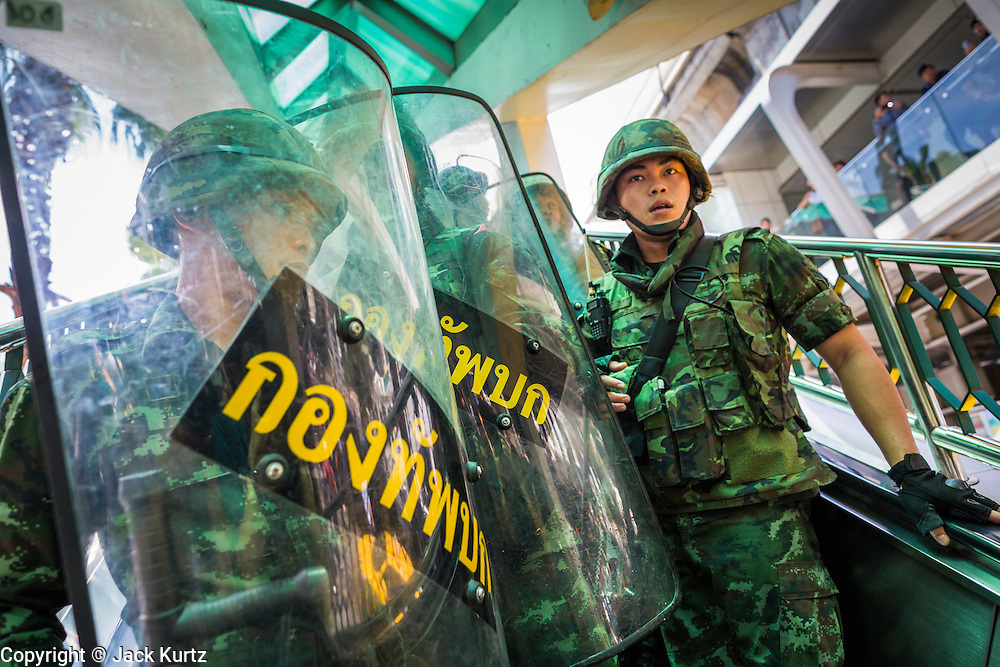 25 MAY 2014 - BANGKOK, THAILAND: Thai soldiers retreat from protestors on an escalator in the BTS Skytrain system. Public opposition to the military coup in Thailand grew Sunday with thousands of protestors gathering at locations throughout Bangkok to call for a return of civilian rule and end to the military junta.     PHOTO BY JACK KURTZ