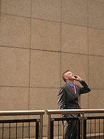 Businessman talking on mobile phone looking up