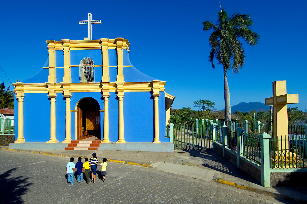 Children cross the street to enter the colonial church of Saint John The Baptist in the town of San Juan de Oriente, one of the 'Pueblos Blancos' or White Towns.  The Mombacho Volcano can be seen in the background.
