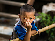 20 JUNE 2016 - DON KHONE, CHAMPASAK, LAOS:  A boy watches a funeral procession in Don Khone village on Don Khone Island. Don Khone Island, one of the larger islands in the 4,000 Islands chain on the Mekong River in southern Laos. The island has become a backpacker hot spot, there are lots of guest houses and small restaurants on the north end of the island.    PHOTO BY JACK KURTZ
