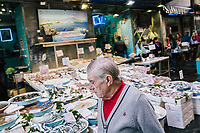 "NAPLES, ITALY - 8 NOVEMBER 2018: An elderly man is seen here by a fish stand in the Pignasecca market  in Montesanto, a neighborhood in the historical center of Naples, Italy, on November 8th 2018.<br /> <br /> The ""citizens' wage"", a welfare policy championed by the governing 5-Star Movement, is designed to lift 5 million Italian out of poverty. The ""citizens' wage"" will cost 10 billion euros next year, the most expensive item in a big-spending budget which itself has raised concerns in the European Union that Italy could be sowing the seeds of a financial crisis."