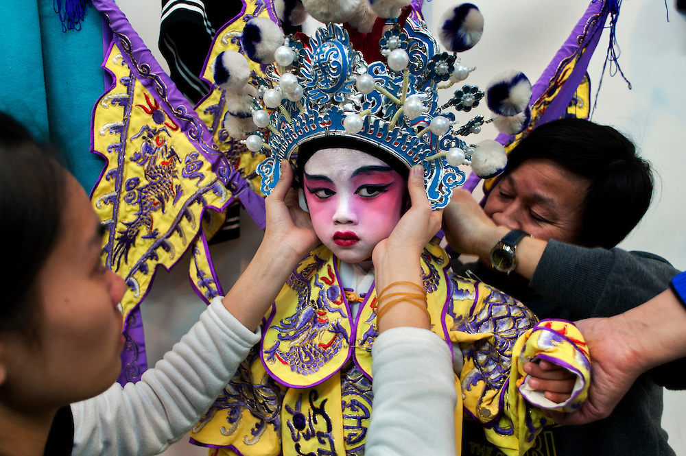Ng Ho (4 year old) from Cha Duk Chang has his general robe getting fixed before a performance. Even for adults assistants are usually needed to fix costumes, heavy headgear or armours.<br />