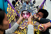 Ng Ho (4 year old) from Cha Duk Chang has his general robe getting fixed before a performance. Even for adults assistants are usually needed to fix costumes, heavy headgear or armours.<br /> <br /> Cha Duk Chang (查篤撐) is a Children's Cantonese Opera Association from Hong Kong that aim is to use the traditional art of Chinese Opera as a method of education and to maintain interest in traditional culture among Hong Kong's children.<br /> <br /> At the end of 2013, the children of Cha Duk Chang performed in Foshan, in the Guangdong province of China, a new original Opera written by Stella Ma, playwright and director of the association, called &quot;Rehearsing for a Great Fun Show&quot;. Unlike traditional Cantonese operas, this opera is designed for children. Its music and lyrics are easy to sing and to memorize.