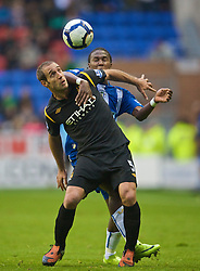 WIGAN, ENGLAND - Sunday, October 18, 2009: Manchester City's Pablo Zabaleta and Wigan Athletic's Jason Scotland during the Premiership match at the JJB Stadium. (Pic by David Rawcliffe/Propaganda)