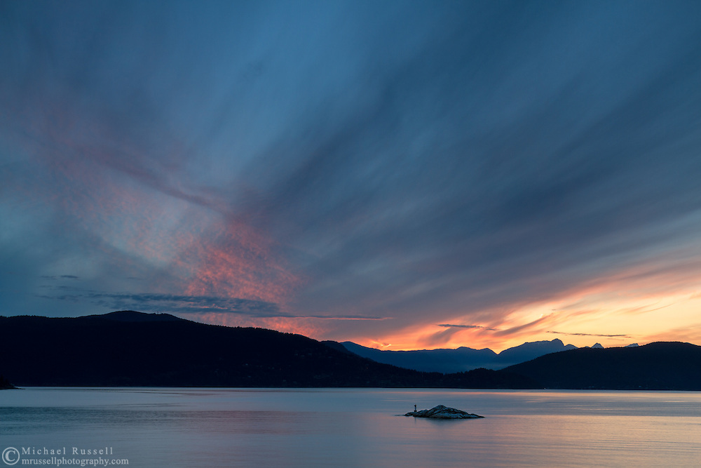 Sunset over Bowen Island, the Grebe Islets, and the mountain peaks in the Sunshine Coast's Tetrahedron Range.  Photographed from Juniper Point at Lighthouse Park in West Vancouver, British Columbia, Canada.