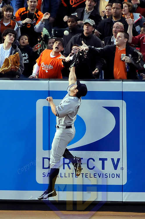 06 April 2009:  New York Yankees left fielder Johnny Damon (18) leaps in an attempt to catch a 2-run home run off the bat of Baltimore Orioles shortstop Cesar Izturis in the 8th inning as fans in the stand reach to catch the ball at Camden Yards in Baltimore, MD.  The Orioles defeated the Yankees 10-5 in the home opener to start the major league regular season.  ****For Editorial Use Only****