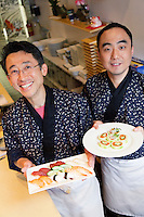 Happy Asian chefs with Japanese cuisines in restaurant
