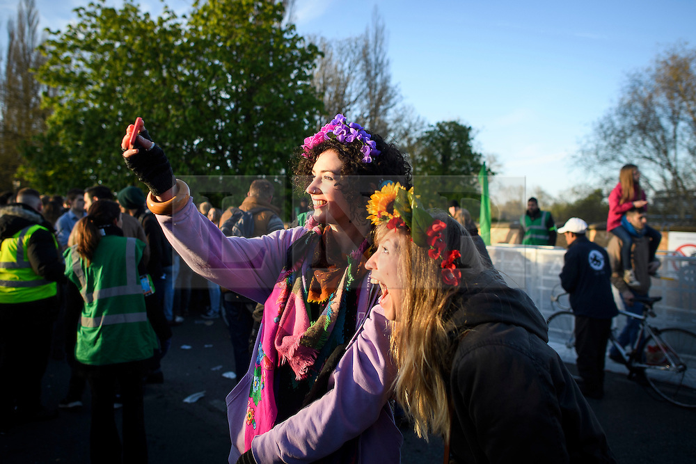 © London News Pictures. 01/05/2016. Oxford, UK. Oxford Two young women wearing flowers in their hair take a picture of themselves during May Day day celebrations in the early hours of the morning near Magdalen Bridge in Oxford, Oxfordshire. This year people were again prevented from jumping from the bridge in to the water due to serious injuries sustained at a previous years event . Photo credit: Ben Cawthra/LNP