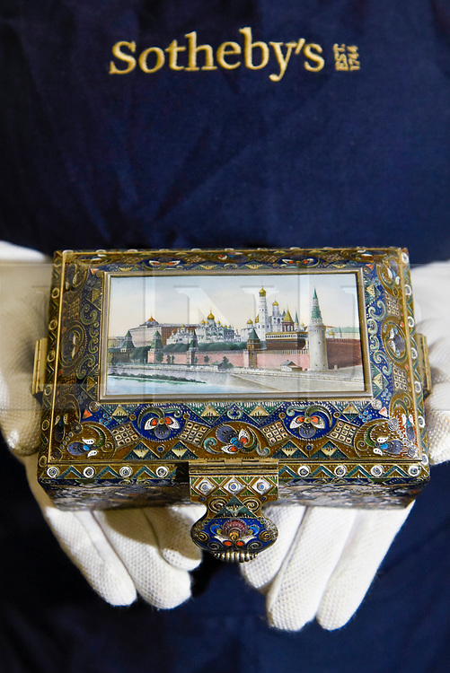 "© Licensed to London News Pictures. 22/11/2019. LONDON, UK. A technician presents ""A silver-gilt, cloisonné and pictorial enamel casket"", 1908-1917, by Feodor Ruckert (Est. GBP100-150k) at the preview for the upcoming sales of Russian artworks at Sotheby's New Bond Street.  The Russian Pictures and Works of Art, Fabergé and Icons sales take place on 26 November.  Photo credit: Stephen Chung/LNP"
