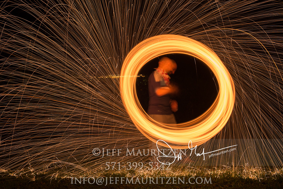 A man spins steel wool that is on fire at nighttime.