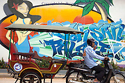 A man is driving a tuk tuk past a colorful sign in Siem Reap, Cambodia.